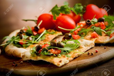 11560119-photo-of-delicious-vegetarian-pizza-with-arugula-on-wooden-table-stock-photo